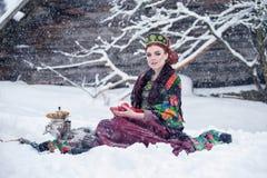 Портрет шикарной молодой женщины в русском платье стиля на сильном заморозке в дне зимы снежном с яблоками и самоваром Стоковая Фотография RF