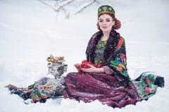 Портрет шикарной молодой женщины в русском платье стиля на сильном заморозке в дне зимы снежном с яблоками и самоваром Стоковое Фото