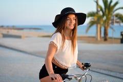 Портрет шикарной счастливой женщины на езде велосипеда на пляже на солнечный день Стоковое Изображение