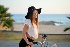 Портрет шикарной счастливой женщины на езде велосипеда на пляже на солнечный день Стоковая Фотография