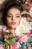 Портрет шикарной чувственной женщины лежа вниз на цветках Стоковая Фотография RF