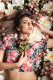 Портрет шикарной чувственной женщины лежа вниз на цветках Стоковое Фото