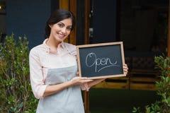 Портрет шильдика удерживания официантки открытого на входе Стоковое Изображение RF
