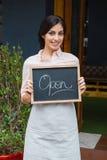 Портрет шильдика удерживания официантки открытого на входе Стоковые Фотографии RF