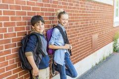 Портрет школы 10 лет мальчика и девушки имея потеху снаружи Стоковые Фотографии RF