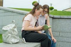 Портрет 2 школьниц подростков с рюкзаками и книгами школы стоковое изображение rf