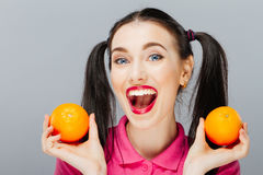 Портрет шуточной счастливой девушки держа оранжевую близко сторону Стоковое фото RF