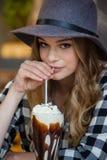 Портрет шляпы молодой женщины нося выпивая холодный кофе Стоковая Фотография RF