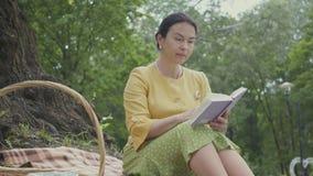 Портрет элегантной красивой зрелой женщины читая книгу сидя на одеяле под деревом в парке wicker акции видеоматериалы