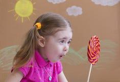 Портрет эмоциональной девушки с большим леденцом на палочке сахара Красивейшая маленькая девочка с lollipop Стоковое Фото