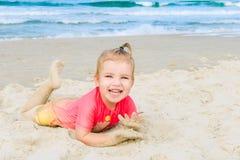 Портрет эмоциональной прелестной девушки малыша в костюме заплывания солнца защищая лежа на песке на пляже и смотря камеру Стоковые Изображения