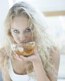 Портрет эмоциональной женщины выпивая травяной чай в доме Стоковое Изображение RF
