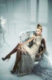 Портрет элегантной белокурой дамы сидя на причудливом кресле Стоковые Изображения