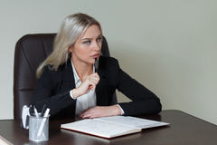 Портрет элегантной коммерсантки в костюме сидя на таблице Стоковое Изображение RF