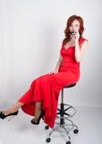 Портрет элегантной молодой женщины redhead в красном платье, имеющ стекло красного вина Стоковая Фотография RF