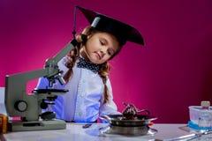 Портрет любознательной девушки представляя в научной лаборатории Стоковые Фотографии RF