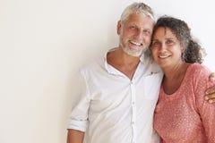 Портрет любящих зрелых пар стоя против стены Стоковые Фотографии RF