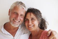 Портрет любящих зрелых пар стоя против стены Стоковое Фото