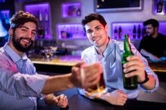 Портрет людей показывая стекло пива и пивной бутылки Стоковое фото RF