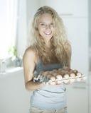 Портрет яичек нося женщины в кухне Стоковое Изображение RF