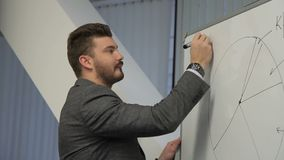Портрет busiessman которое пишет цифровую ситуацию валютного рынка на whiteboard на конференции сток-видео