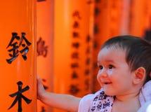 Портрет cherful маленького младенца с красными красочными toriis святыни Fushimi Inari Taisha на предпосылке Стоковые Изображения RF