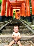 Портрет cherful маленького младенца с красными красочными toriis святыни Fushimi Inari Taisha на предпосылке, Киото, Японии Стоковая Фотография RF