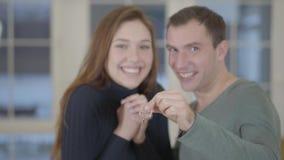 Портрет cherful счастливой женатой пары показывая ключи купленных нового дома или квартиры к камере и сток-видео