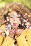 Портрет confetti красивой женщины дуя в воздухе стоковые изображения