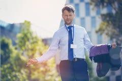 Портрет confused бизнесмена стоя с блейзером Стоковое Изображение