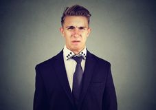 Портрет disgusted бизнесмена изолированного на серой предпосылке стены Стоковые Изображения
