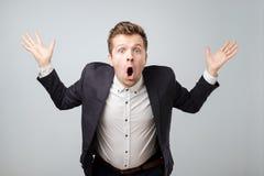 Портрет excited молодого мужчины в костюме кричащем в ударе и изумлении держа руки вверх стоковые фотографии rf