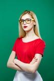 Портрет Eyeglasses девушки Seriuos нося, красный верх и юбка белизны на зеленой предпосылке Молодая красивая женщина с Стоковое фото RF