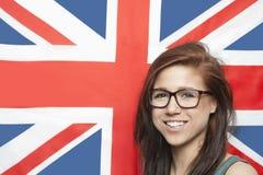 Портрет eyeglasses жизнерадостной молодой женщины нося против британцев сигнализирует стоковые изображения rf