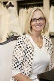 Портрет eyeglasses счастливой старшей женщины нося сидя в bridal бутике Стоковое Изображение