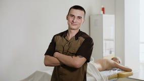 Портрет masseur с оружиями пересек положение в курорте Физический терапевт в медицинском офисе Косметика, массаж сток-видео
