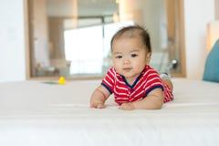 Портрет newborn азиатского младенца на кровати стоковое изображение