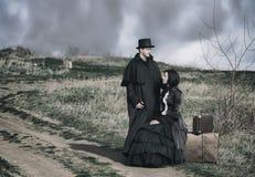 Портрет Outdoors викторианской дамы в черном усаживании на дороге с ее багажом и джентльменом стоя рядом стоковое изображение