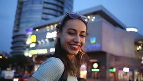 Портрет Outdoors городской молодой взрослой красивой женщины в стеклах, представляя outdoors на улице на светах города ночи сток-видео