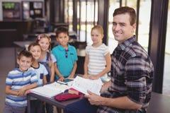 Портрет schoolkids учителя уча в библиотеке Стоковое фото RF