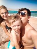 Портрет Selfie родителей целуя маленького сына малыша на пляже моря на солнечном ветреном дне Семья ослабляя и имея стоковые фотографии rf