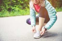 Портрет sporty белокурой девушки в наушниках на беге в усаживании девушки леса a связал шнурки на беге по пересеченной местности Стоковые Фотографии RF