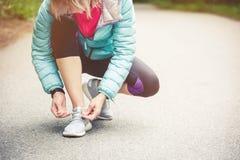 Портрет sporty белокурой девушки в наушниках на беге в усаживании девушки леса a связал шнурки на беге по пересеченной местности Стоковое Фото