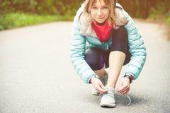 Портрет sporty белокурой девушки в наушниках на беге в усаживании девушки леса a связал шнурки на беге по пересеченной местности Стоковое Изображение
