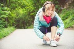 Портрет sporty белокурой девушки в наушниках на беге в усаживании девушки леса a связал шнурки на беге по пересеченной местности Стоковые Фото