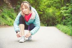 Портрет sporty белокурой девушки в наушниках на беге в усаживании девушки леса a связал шнурки на беге по пересеченной местности Стоковые Изображения RF