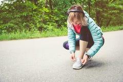 Портрет sporty белокурой девушки в наушниках на беге в усаживании девушки леса a связал шнурки на беге по пересеченной местности Стоковое фото RF