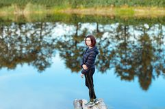 Портрет sporty красивой взрослой женщины брюнет парк города падения представляя около голубого озера с отражениями деревьев осени Стоковые Изображения RF