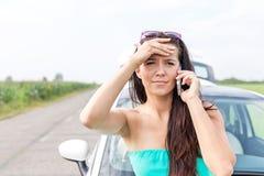 Портрет tensed женщины используя сотовый телефон против сломанный вниз с автомобиля на дороге Стоковая Фотография