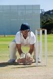 Портрет wicketkeeper заискивая за пнями на поле стоковое изображение